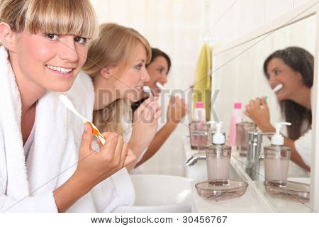 Females roommates brushing teeth