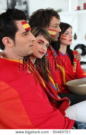 portrait of Spanish supporters watching soccer match on telly