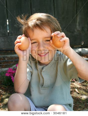 Young Boy Holding Up Two Eggs