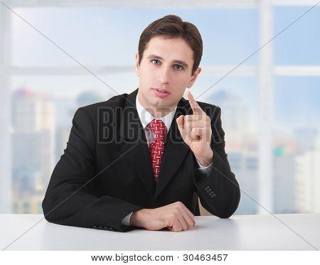 Exitoso hombre de negocios serio, sentado en un escritorio en su oficina y el dedo índice