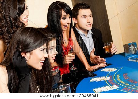 Group of young happy people sitting in casino behind black jack table