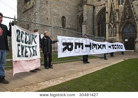 The huge Occupy Exeter banner is unfurled and displayed in front of Exeter Cathedral