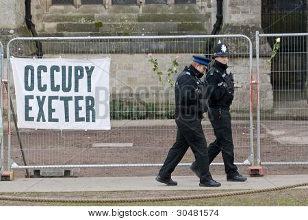 Policemen walk past an Occupy Exeter banner