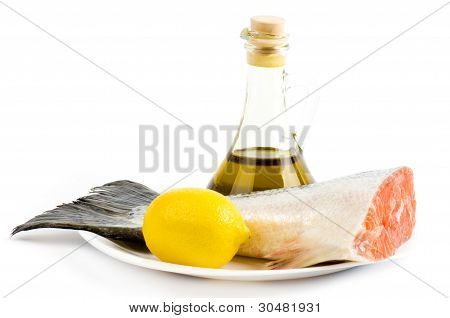 A piece of salmon with vegetables and olive oil on a white background