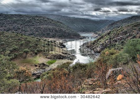 Spanish landscape with river on a stormy day