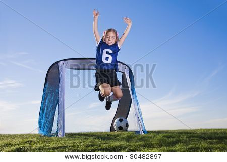 Young Girl playing soccer and scoring goal