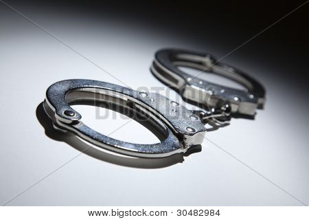 Abstract Pair of Handcuffs Under Spot Light on Gradated Background.