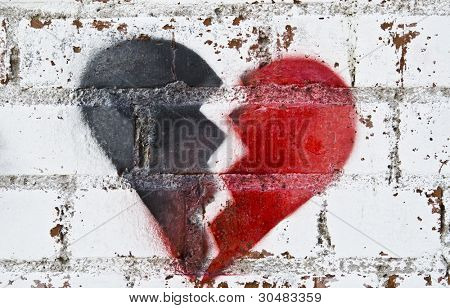 Two parts of broken heart spray painted on grungy wall.