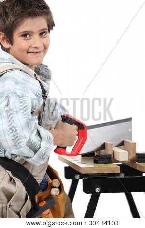 Young boy dressed as an adult carpenter cutting wood with a saw
