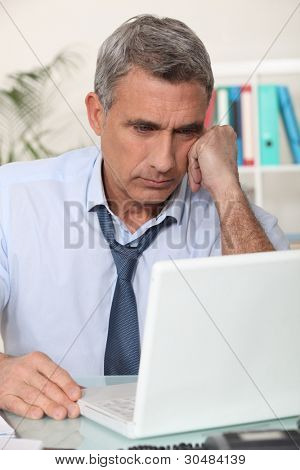 mature man working home with laptop