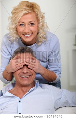 Woman covering her husband's eyes with her hands