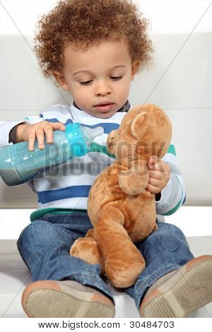Little boy feeding teddy bear from bottle