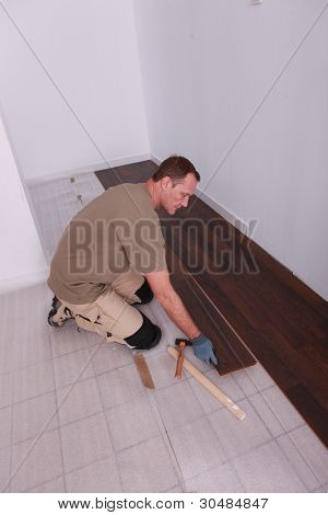 Man laying laminate flooring panels