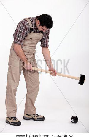 Man smashing piggy-bank with sledge-hammer