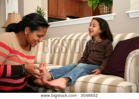 Picture or Photo of Mom tickles her daughter while on the couch