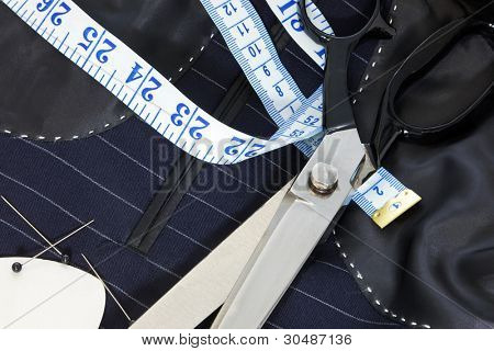 Still life photo of the inside of a bespoke suit jacket with hand stitching and scissors, tape measure, chalk and pins.