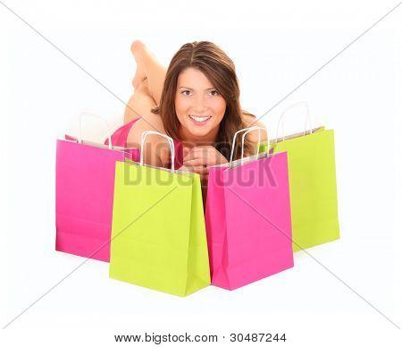 ein Bild von eine hübsche junge Frau liegend unter Einkaufstaschen over white background