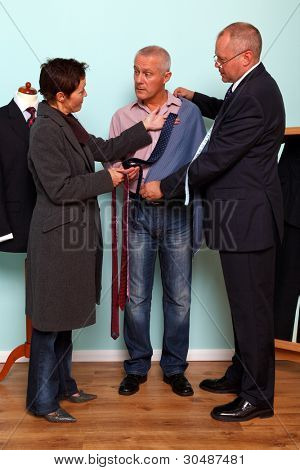 Photo of a man getting advice from his wife during a tailored bespoke suit fitting.