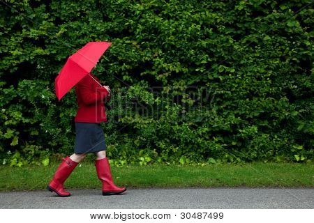 Photo of a woman in red walking along a road with her umbrella up as it starts to rain on an overcast day. Slight motion blur on her legs.