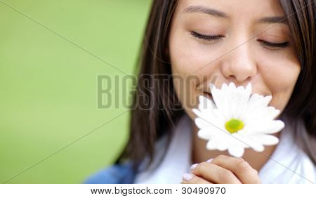 Beautiful woman portrait smelling a flower outdoors