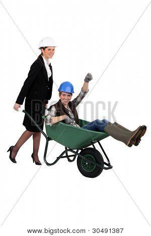 Woman pushing fellow worker in wheelbarrow