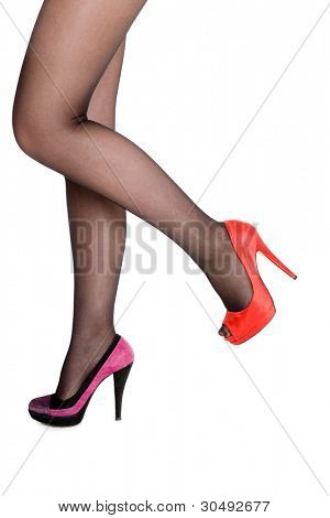 Slender women's legs in pantyhose and different shoes.