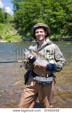 Happy fisherman keeps caught masu salmon (or cherry salmon). Russia. Primorskiy  kray.