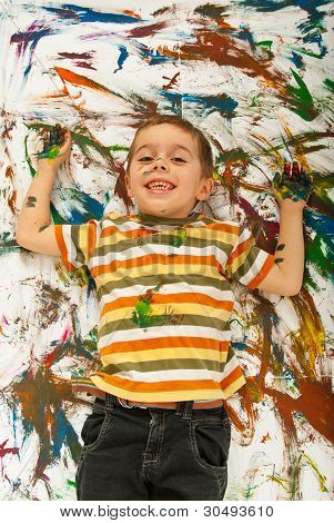 Happy Messy Boy Lying On Panted Background