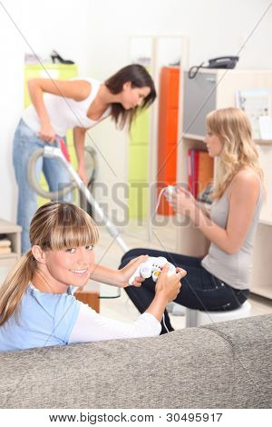 two girls playing video games while their roommate is cleaning the house