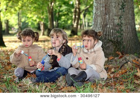 three little girls playing with soap bubble solutions in the forest