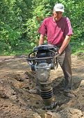 Man uses compactor to firm soil at worksite