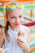 Adorable girl eating chocolate ice cream outdoors on summer day poster