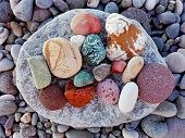 Pile Of Colorful Pebble Stones On Rock Pattern Background. Different Forms Multicolor Pebbles (green poster