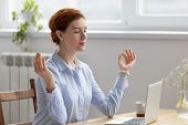 Young Pretty Businesswoman Meditating, Doing Breathing Exercises In Office poster