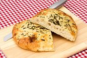 A Loaf Of Homemade Focaccia Bread A Loaf Of Homemade Focaccia Bread On A Wooden Bread Board poster