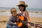 Mom learns(teaches) to play the son on a guitar. Above the sea a fog.