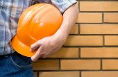 stock photo of bricklayer  - The  bricklayer on a background of a brick wall - JPG