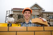 The bricklayer holds a brick in a hand. A builded house.