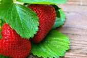 Two Glistining Strawberries On Weathered Wood poster