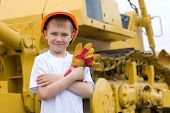 Boy in a helmet is against the background of a large excavator.