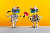 Dates Robots. Romantic Robot Man Gives A Bouquet Of Pink Roses Flowers To A Female Robot. Dating Age poster