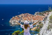 Happy Girl Enjoys View Of Old Town (medieval Ragusa) And Dalmatian Coast Of Adriatic Sea In Dubrovni poster