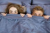 Happy Couple Hiding Under Blanket In Bed . Couple In Bedroom In The Morning. poster