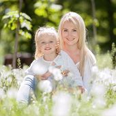 Happy mother and daughter relaxing in the park. Beauty nature scene with family outdoor lifestyle at poster