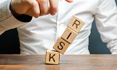 A Businessman Knocks Down A Tower Of Cubes With The Word Risk. Risk Management, Cost Assessment, Bus poster
