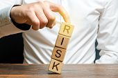 Businessman Rescues With His Finger A Tower Of Cubes With The Word Risk From Falling Risk Management poster