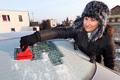 image of ice-scraper  - Woman scraping ice from the car window - JPG