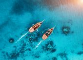 Aerial View Of The Fishing Boats In Transparent Blue Water At Sunset In Summer. Top View From Drone  poster