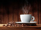 stock photo of coffee-cup  - Cup of coffee with coffee beans on a beautiful brown background - JPG