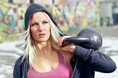 image of kettlebell  - Young determined fitness woman lifting a heavy weight outside in the snow - JPG
